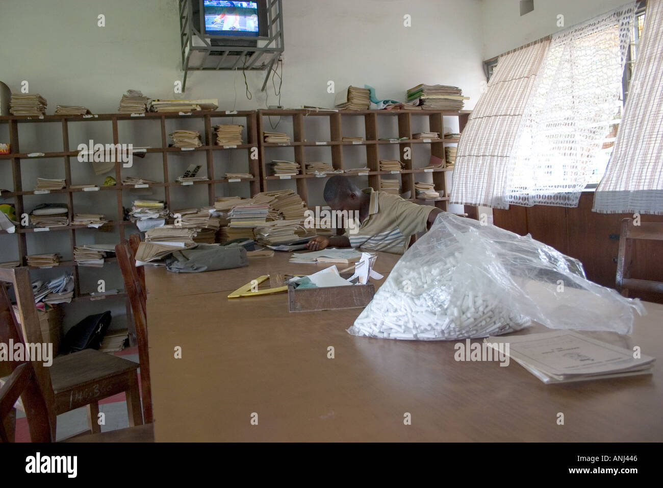 Teacher marking exercise books in the staffroom of a secondary school in Ghana - Stock Image
