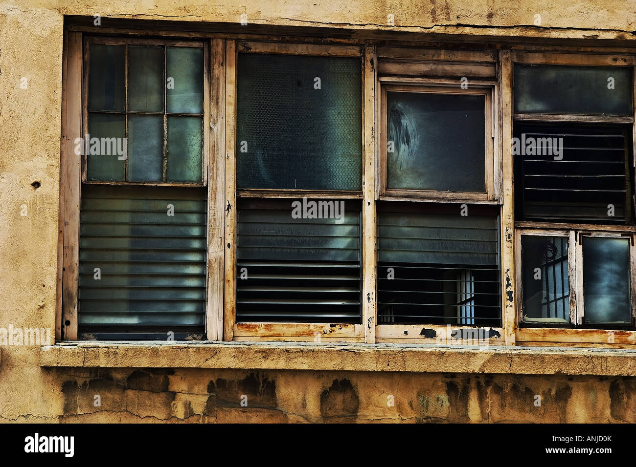 Four louvered, decaying, wood frame windows in a stained and cracked ...