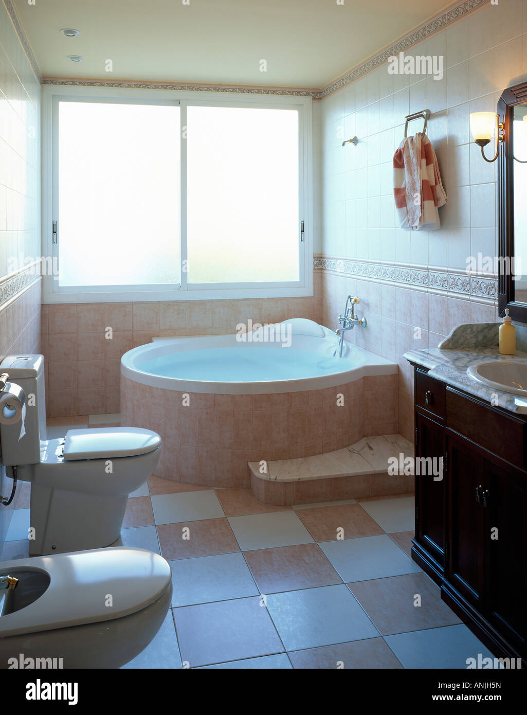 Elegant bathroom with tile surround bath tub commode and tiled floor ...