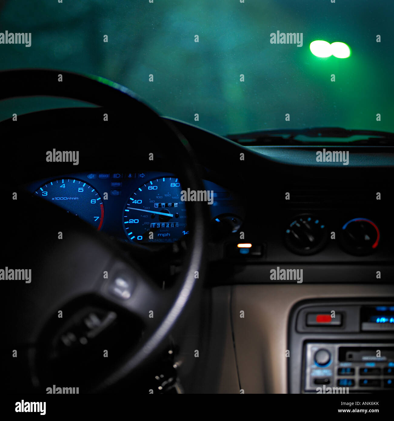 Headlight of approaching car through the windshield of other car with some interior elements and dashboard lights - Stock Image