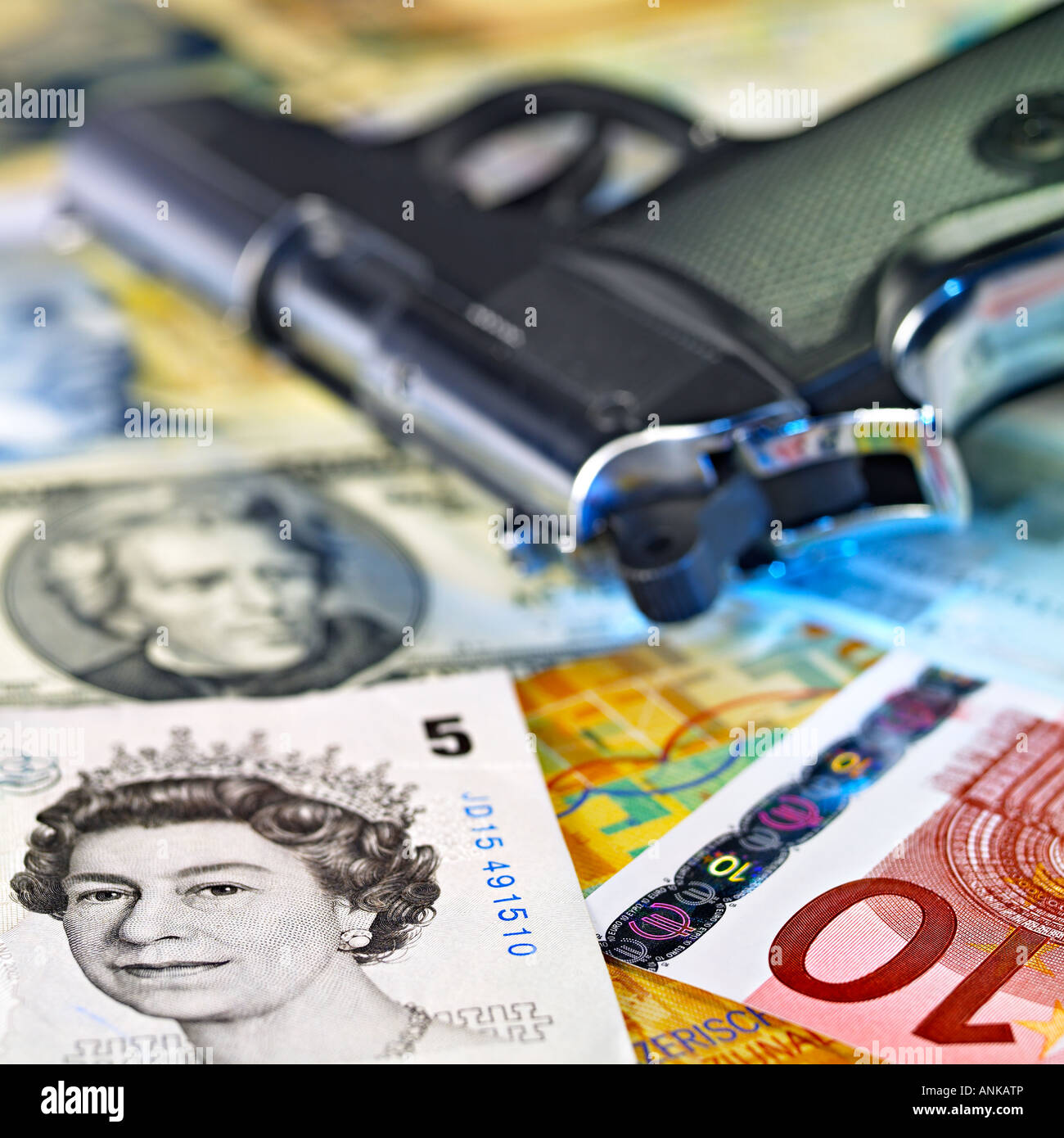 Handgun lying over the foreign currency banknotes - Stock Image