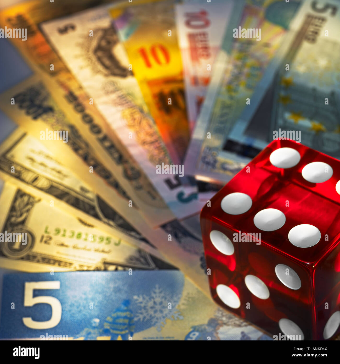 Red die over the different banknotes - Stock Image