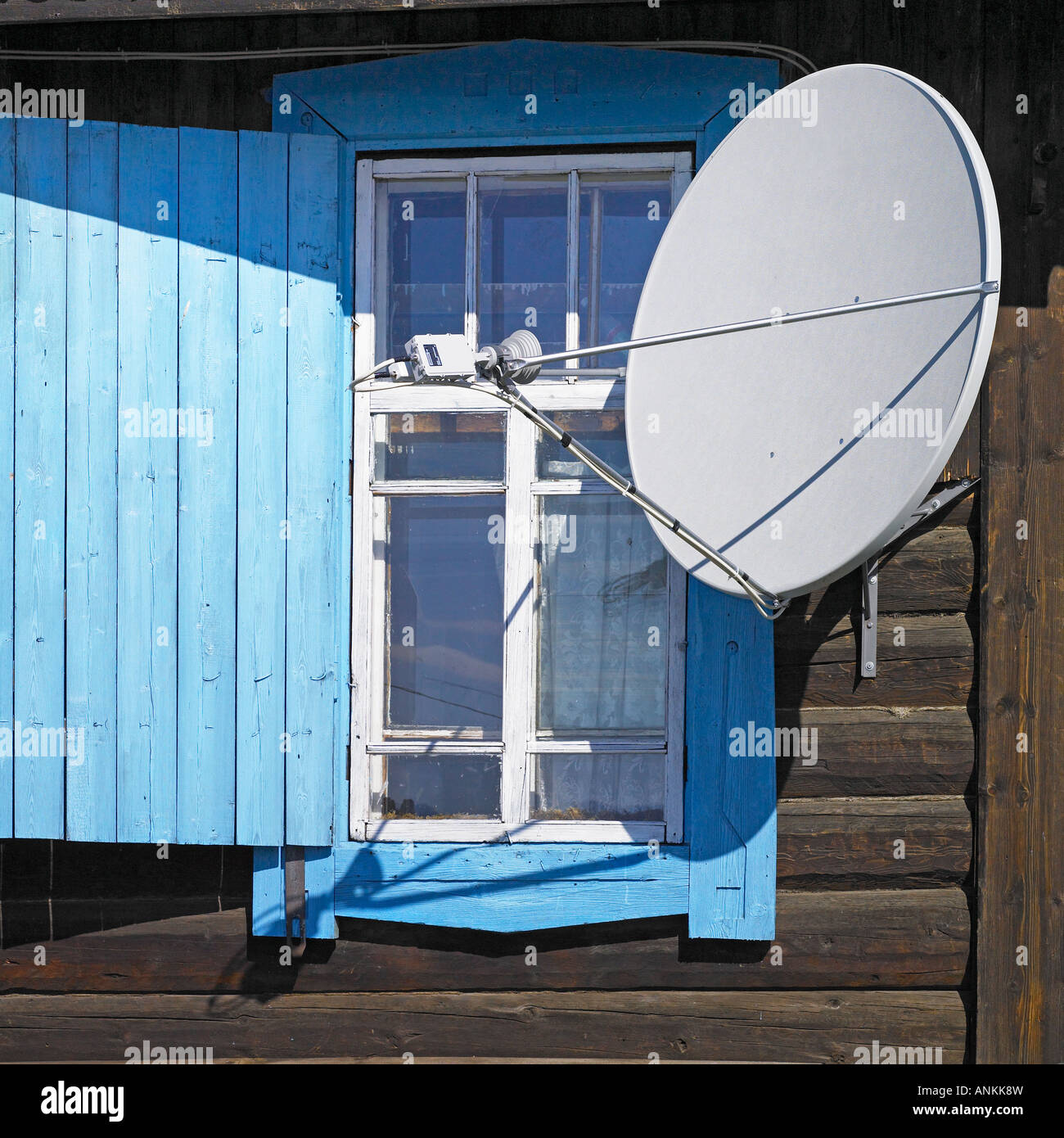 Satellite dish at the log house izba on Russian window in Siberia village - Stock Image