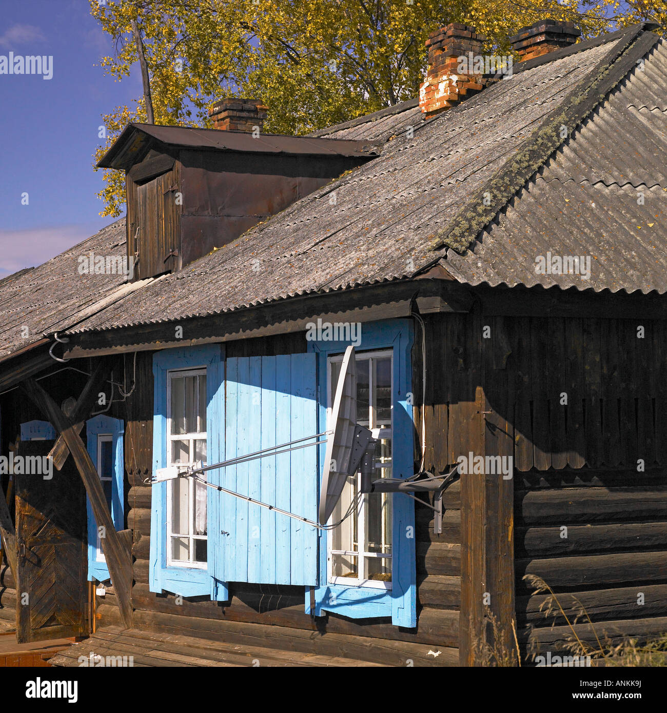 A small log house with a satellite dish - Stock Image