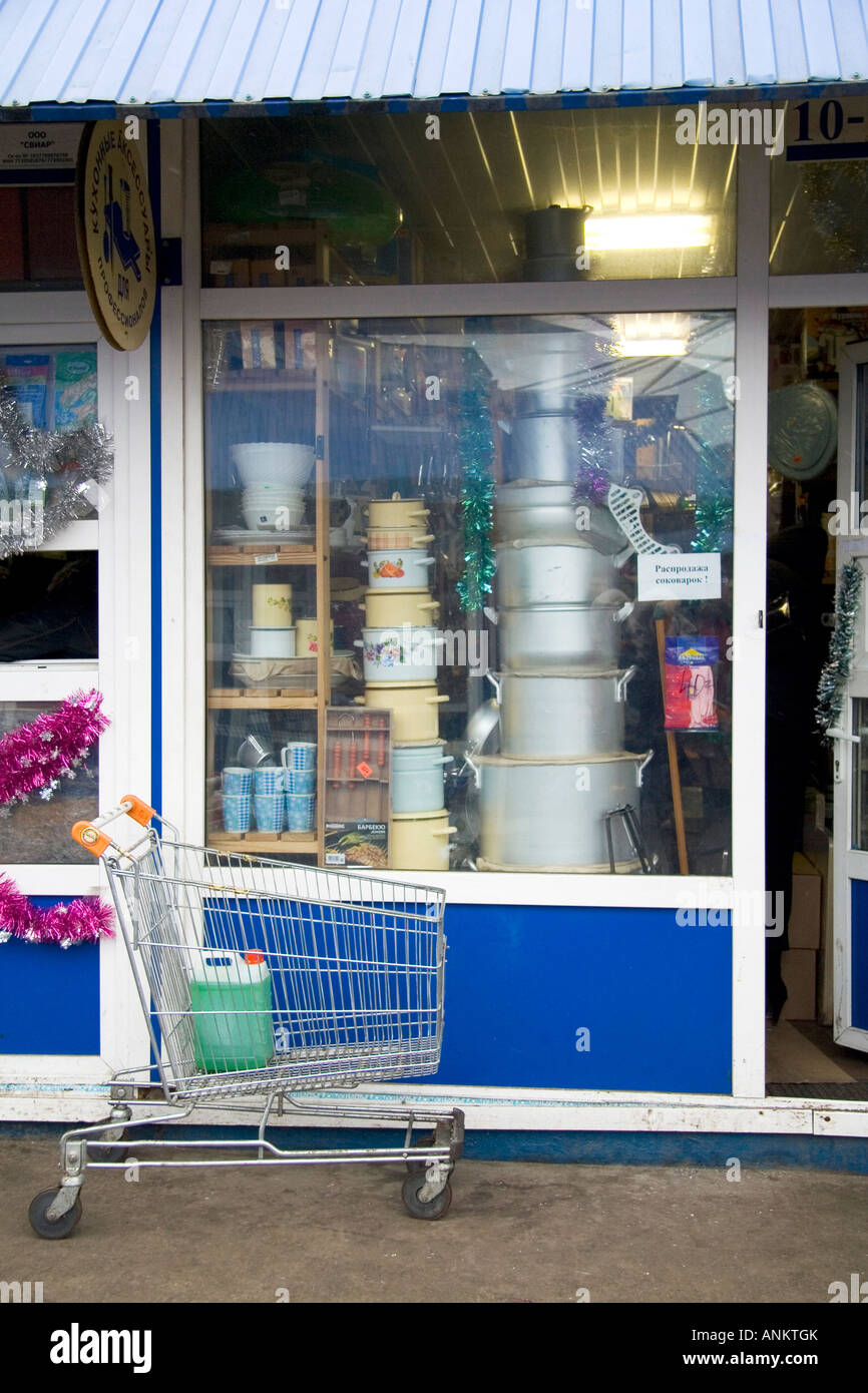 empty shopping trolley in front of shop, tall window display. Display is filled to the top with 'family sets' - Stock Image