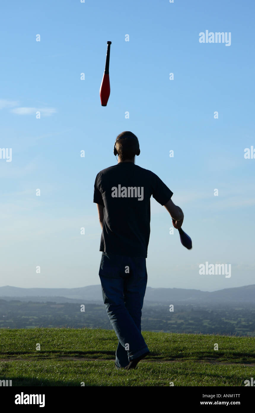 Juggler on a hill top at dusk. - Stock Image