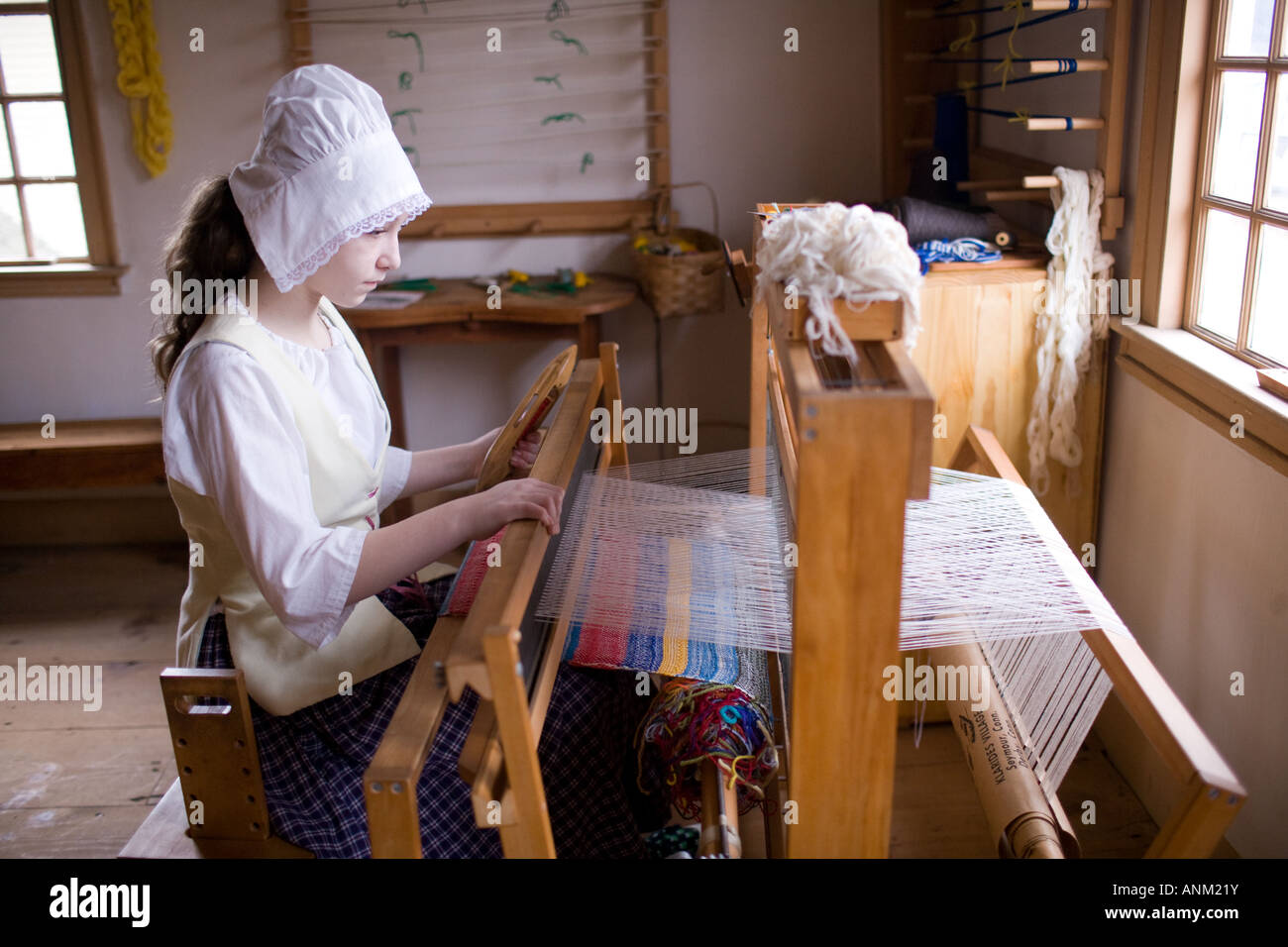 A young girl dressed in period garb demonstrates weaving at the David Humphry House in Ansonia Connecticut, USA - Stock Image