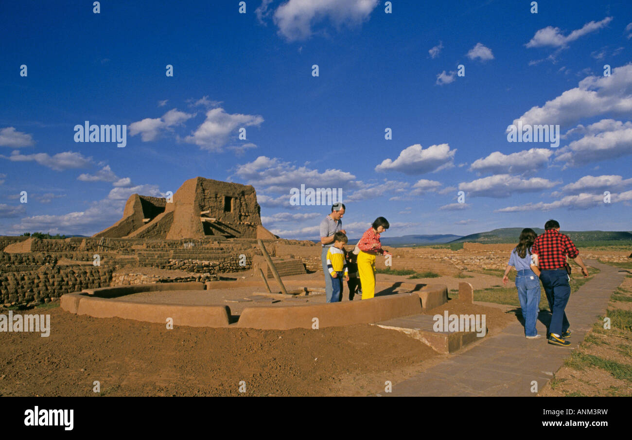 Visitors explore the adobe ruins of an old Spanish mission and an Anasazi Indian town at Pecos National Historical - Stock Image