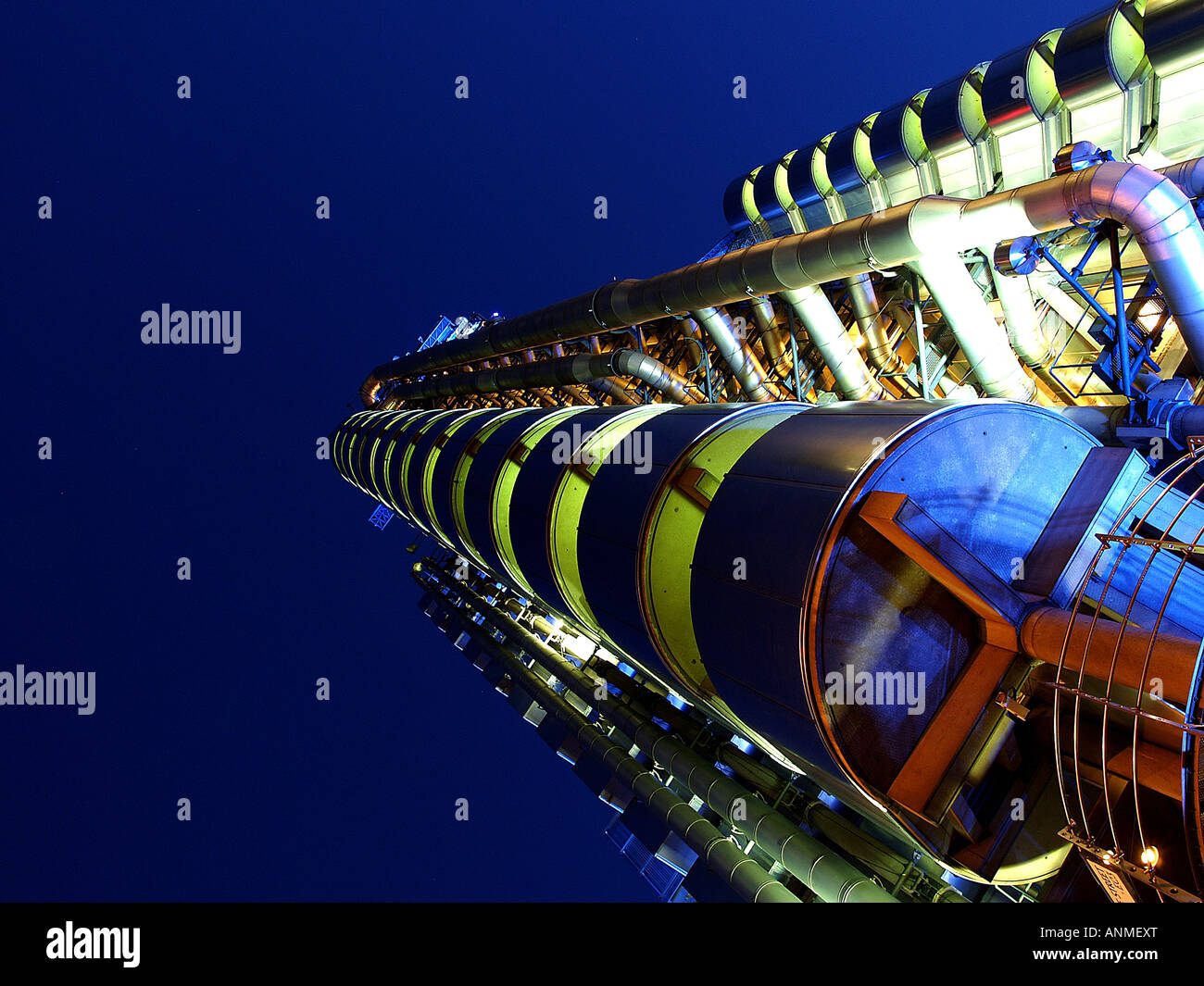Ground level dramatic shot of Lloyds of London building at night with vivid colours - Stock Image