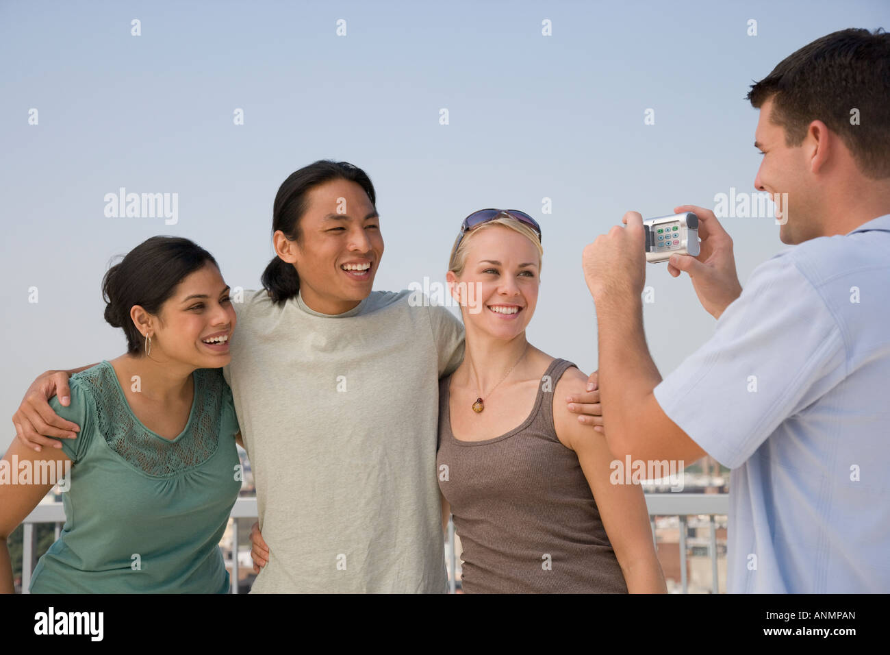 Multi-ethnic friends having photograph taken - Stock Image