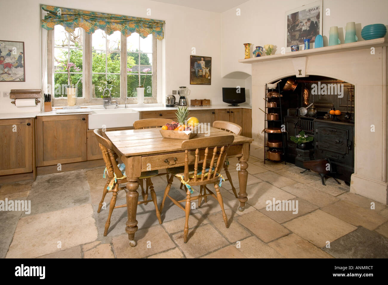 Home interior, simple modern kitchen with dining table and old cooking range feature. - Stock Image