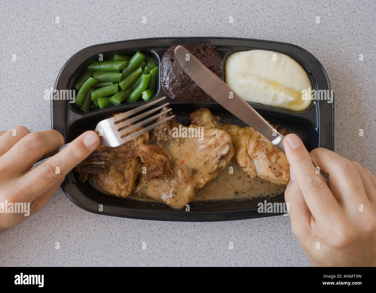 Man eating TV dinner - Stock Image