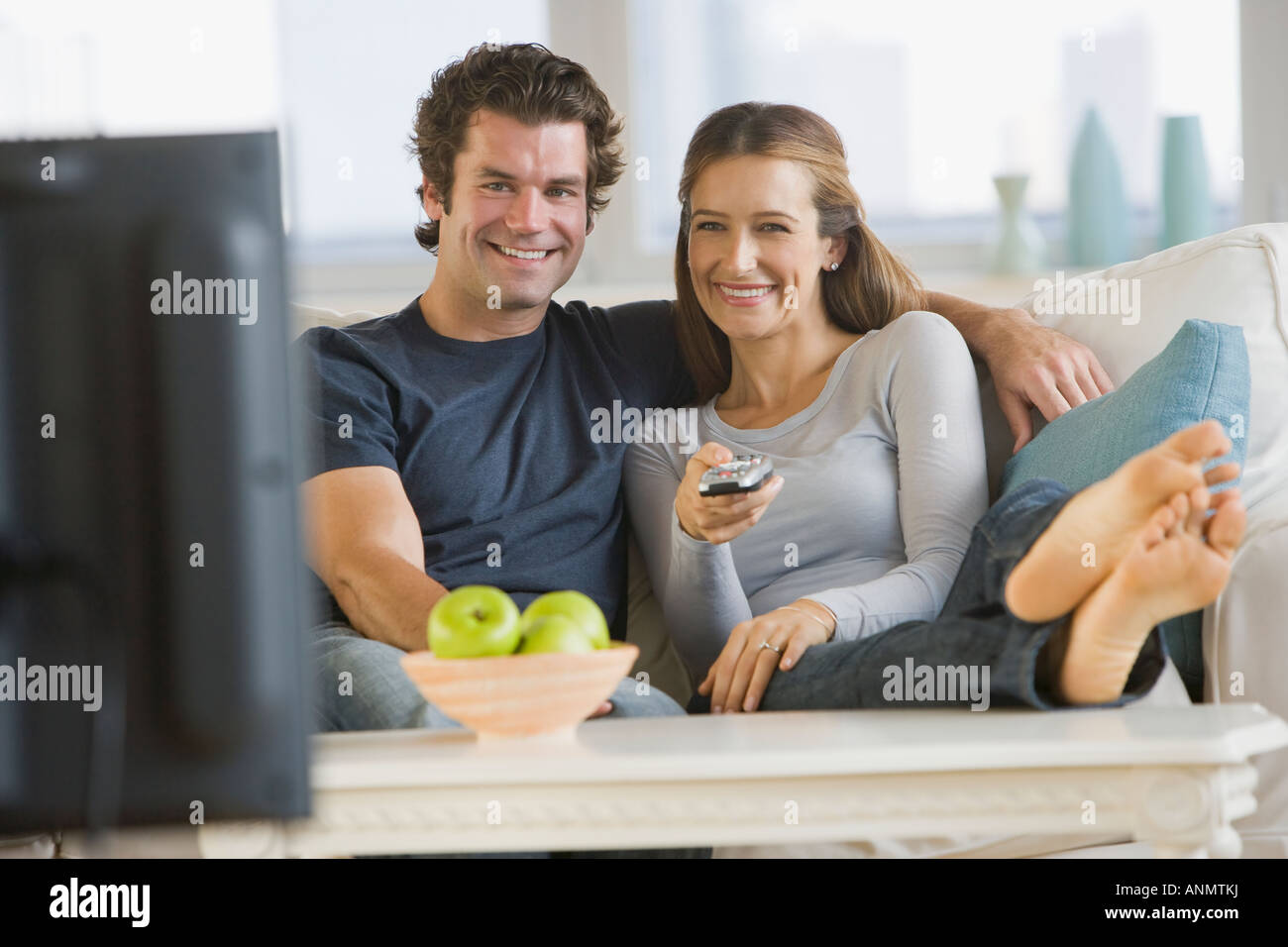 Couple watching television on sofa - Stock Image