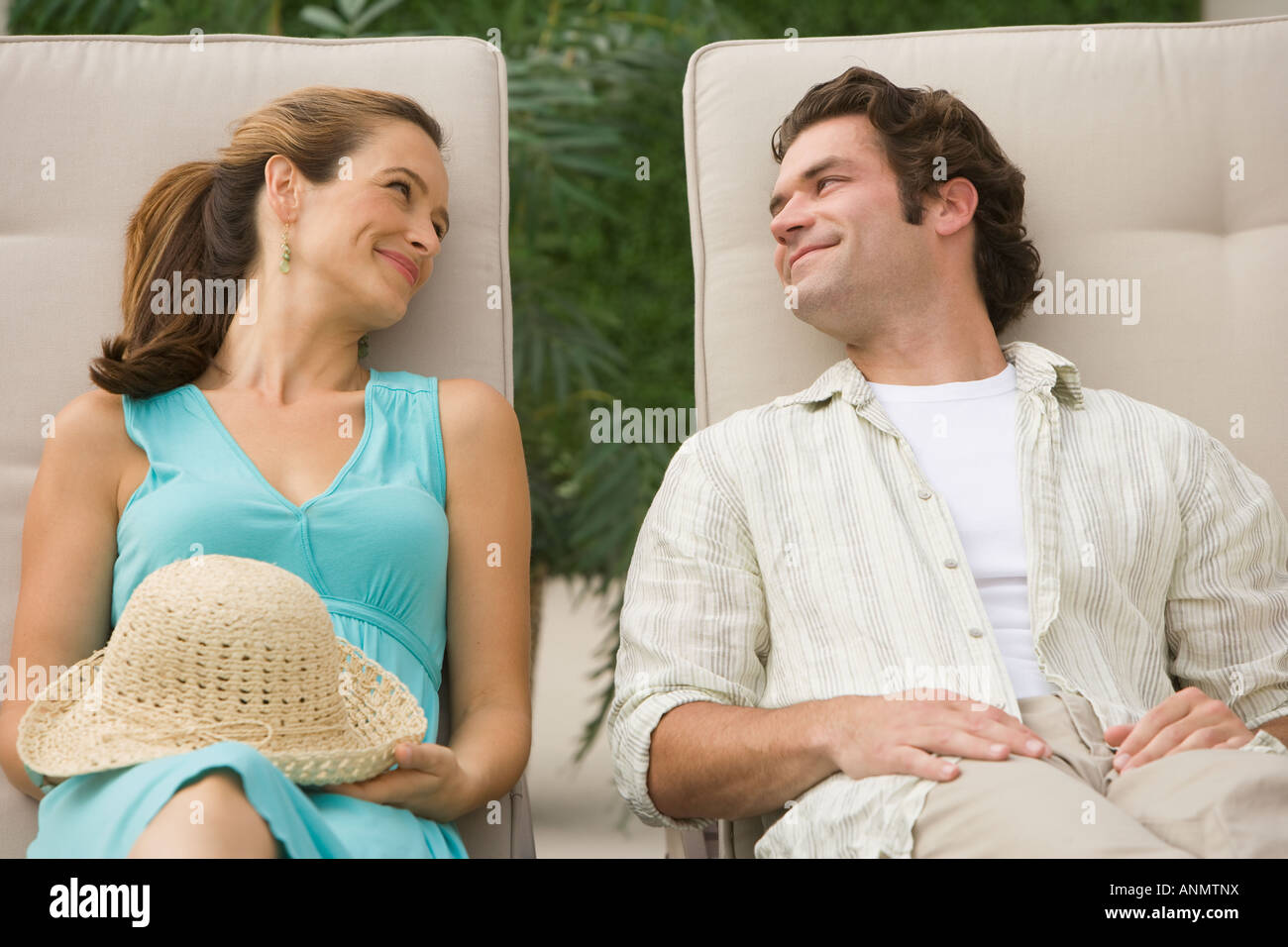 Couple laying in lounge chairs Stock Photo