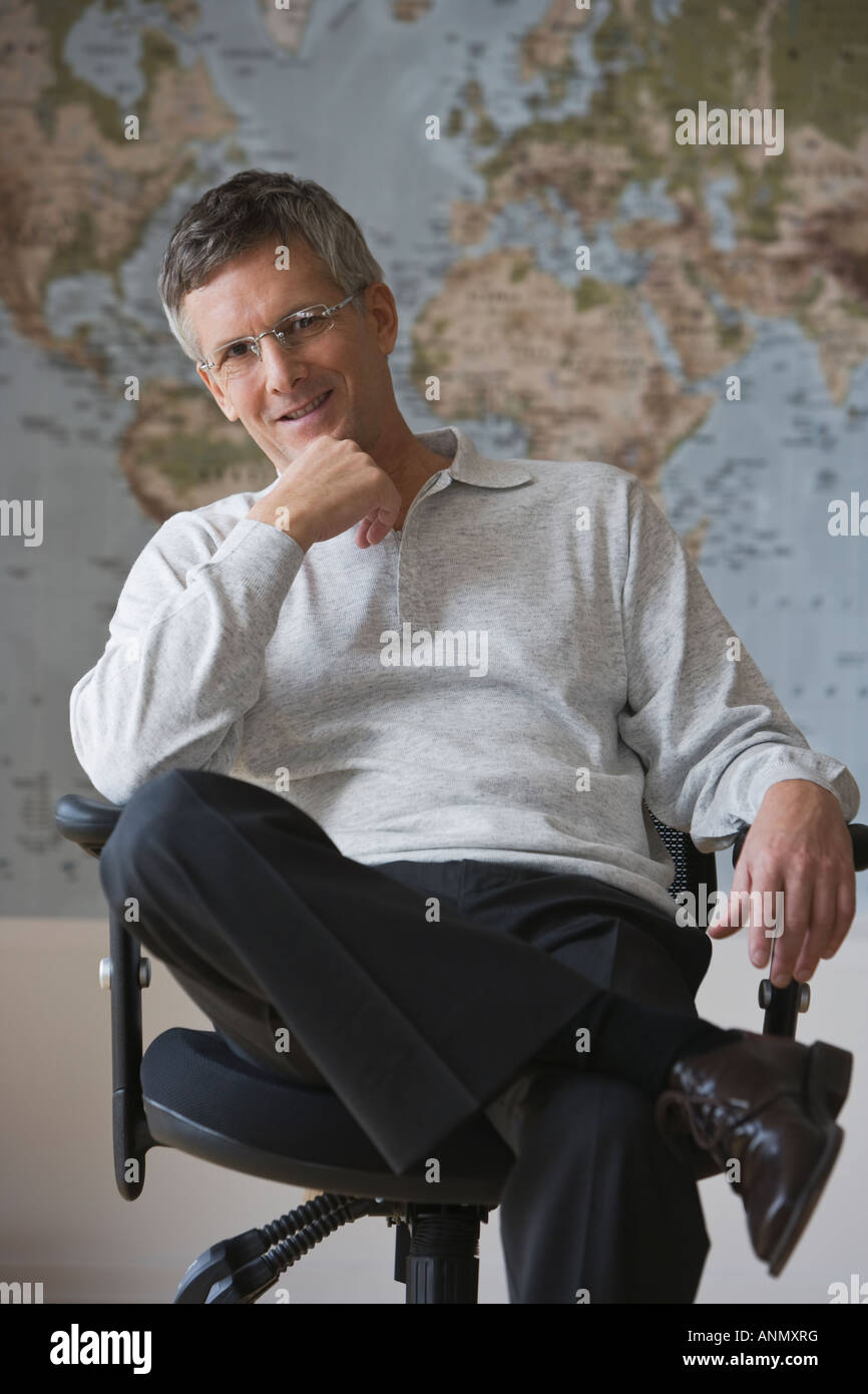 Businessman sitting in front of world map - Stock Image