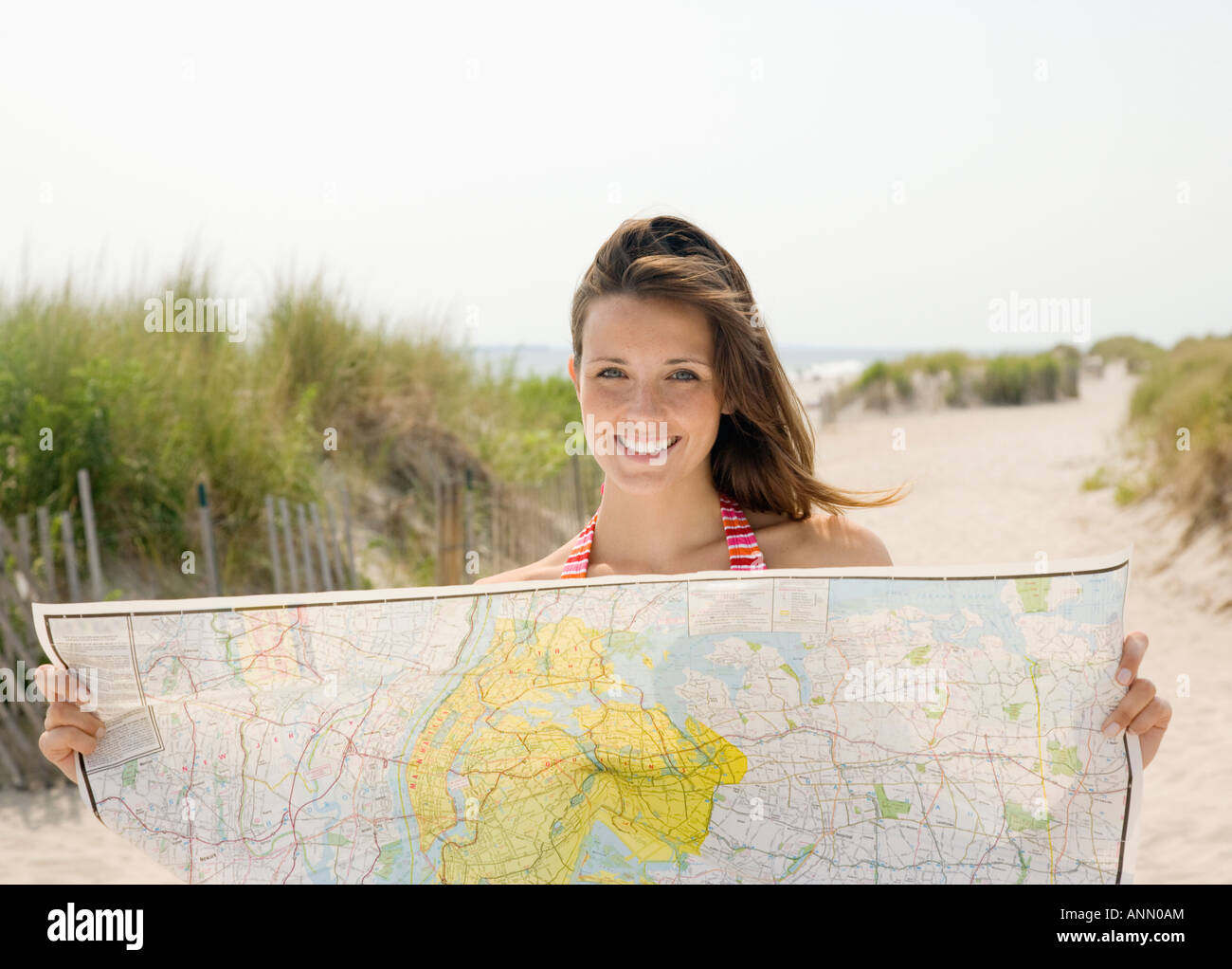 Woman holding map at beach - Stock Image