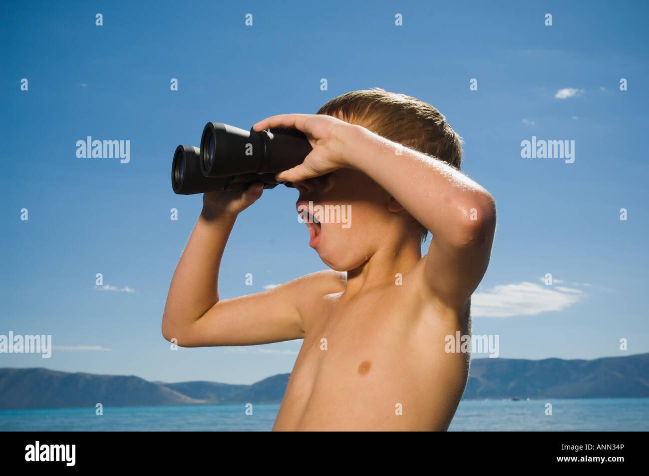 Boy looking through binoculars, Utah, United States - Stock Image