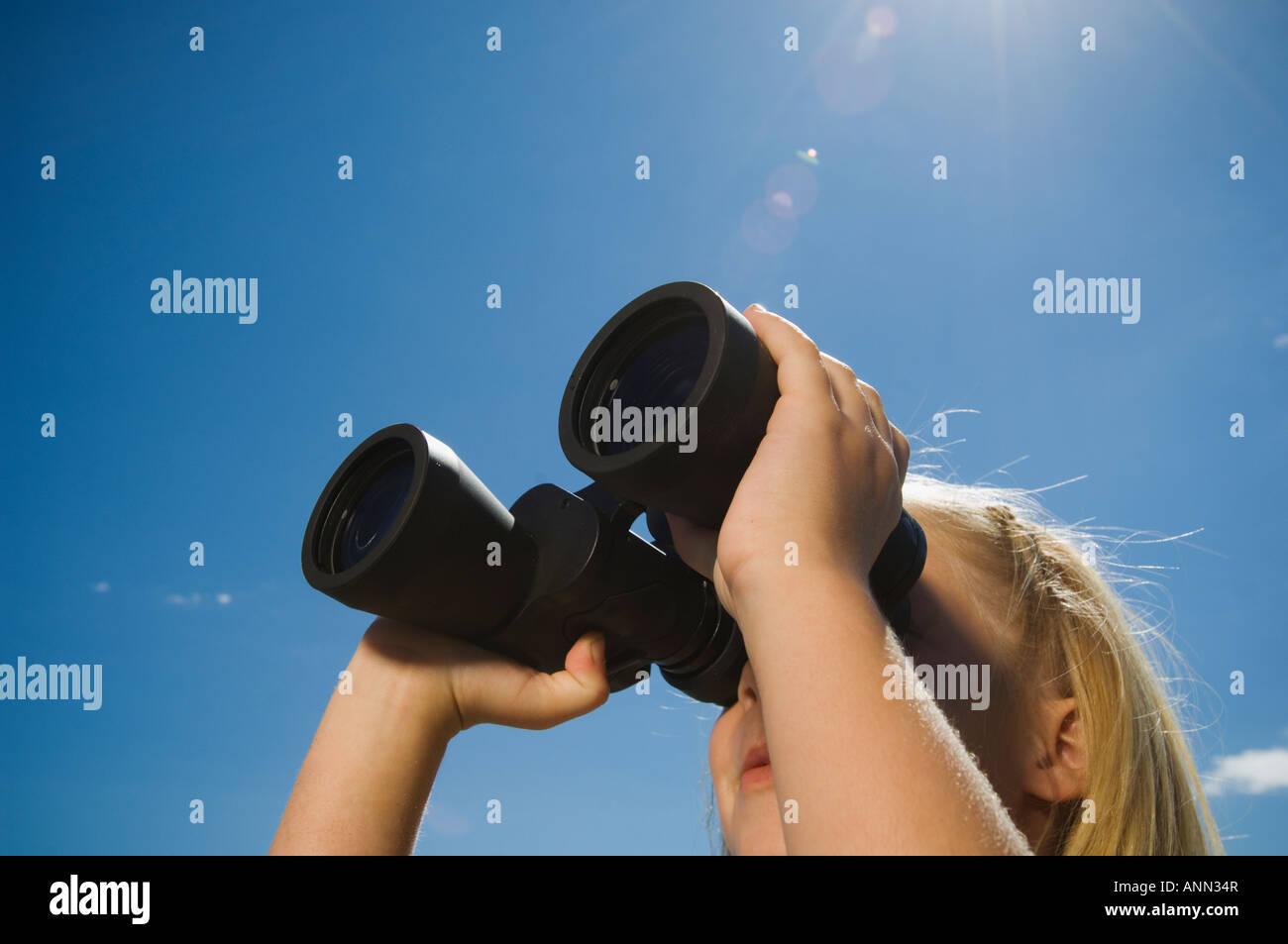 Girl looking through binoculars, Utah, United States - Stock Image