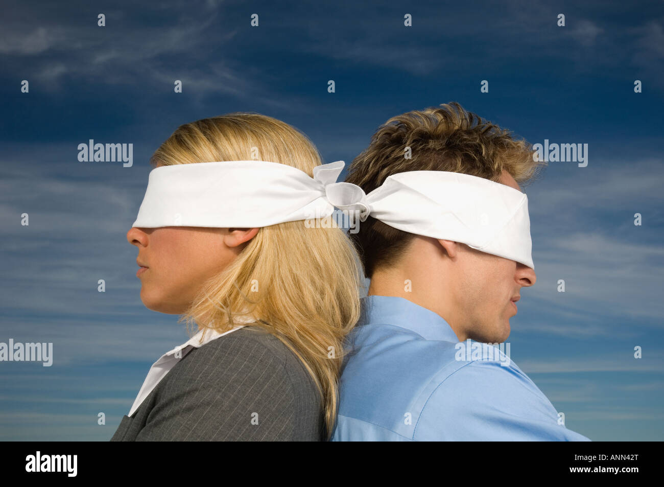 Blindfolded businesspeople standing back to back, Salt Flats, Utah, United States - Stock Image
