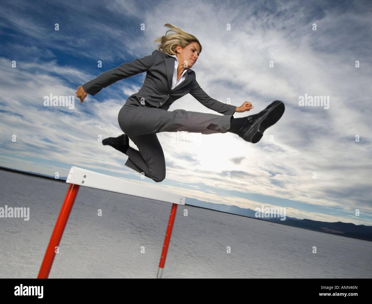 Businesswoman jumping over hurdle, Salt Flats, Utah, United States - Stock Image
