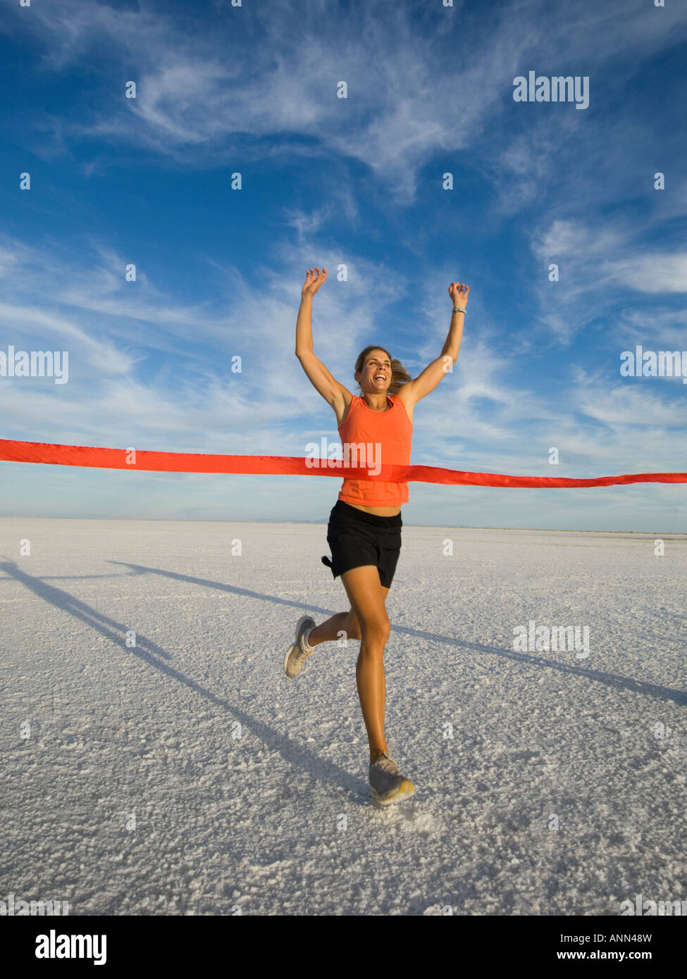 Woman running across finish line, Utah, United States - Stock Image