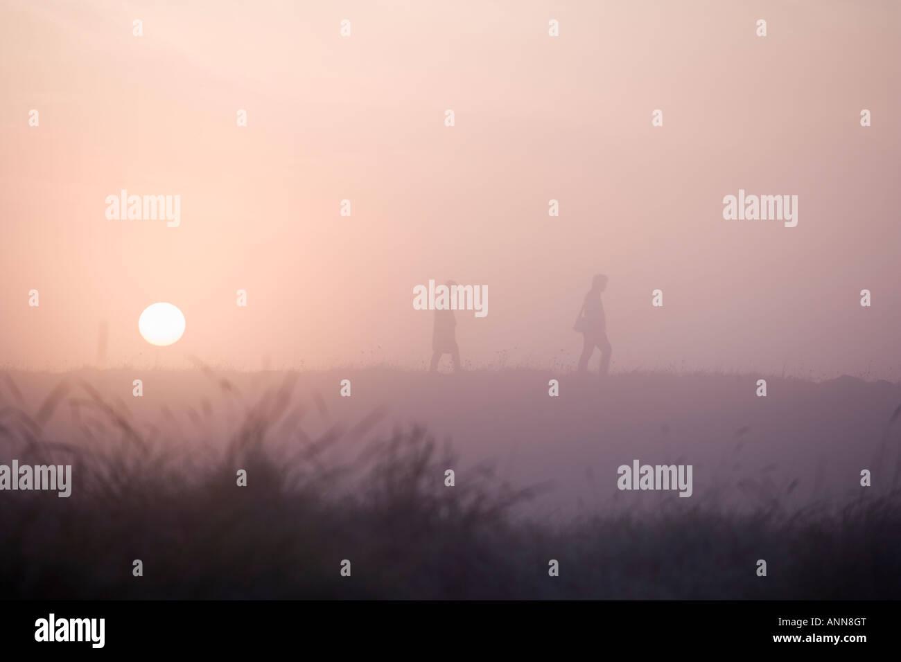 couple taking a walk at sunrise Stock Photo
