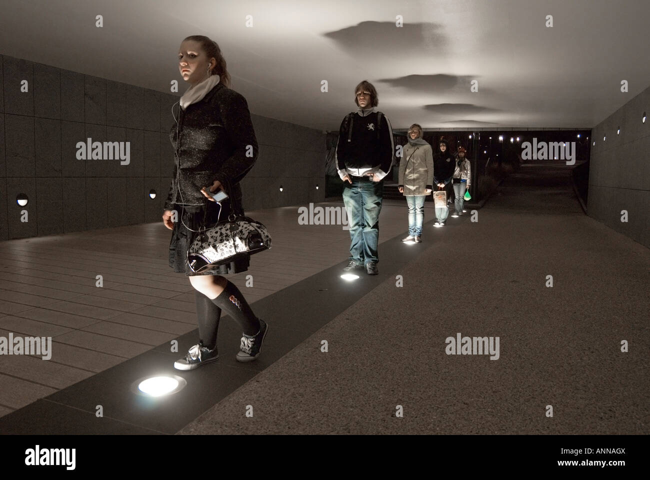 Group of American teenagers stand in a pedestrian underpass at night - Stock Image