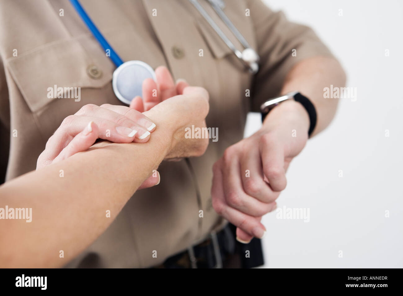 View of Emergency Medical Service officer checking the pulse of a patient. Stock Photo