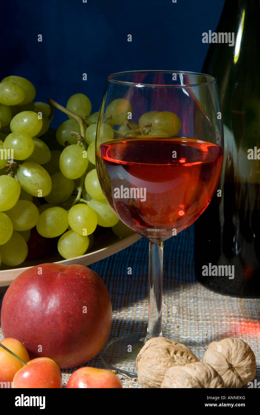 Classic still life featuring a colorful bowl of fruit and a wine bottle with a wineglasses on a black background - Stock Image