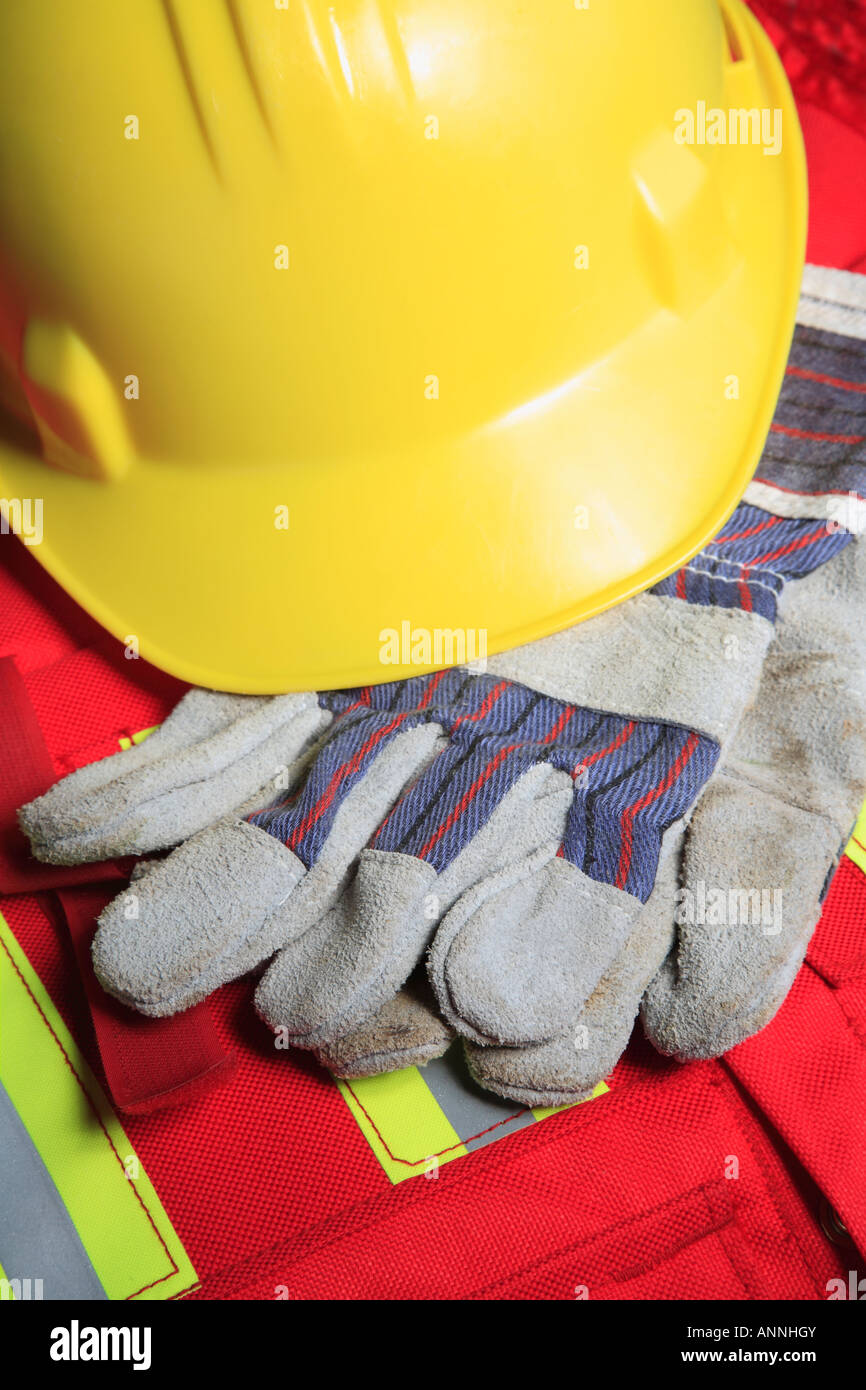 Work concept with hard hat gloves on safety vest - Stock Image