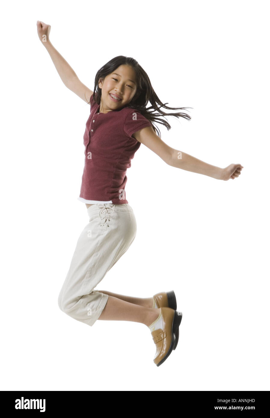 Portrait of a teenage girl jumping with her arms outstretched - Stock Image