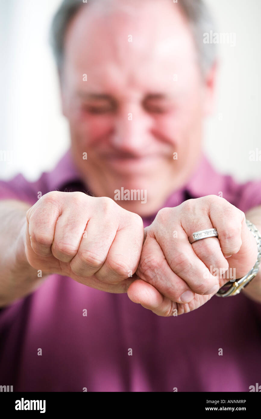 View of a mature man holding hands to be tied. - Stock Image