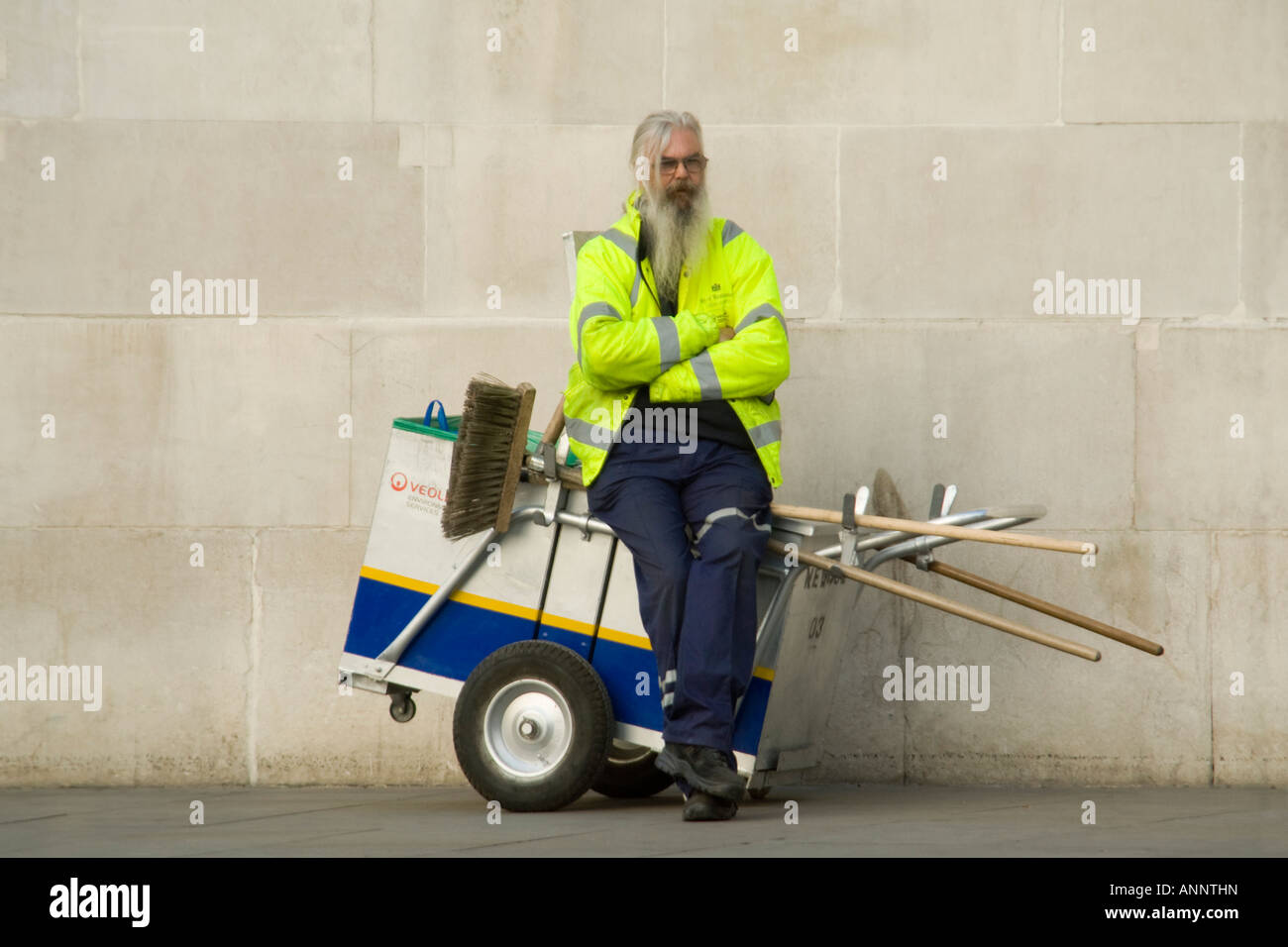 Horizontal close up portrait of a council street cleaner sitting on his cart having a break. Stock Photo