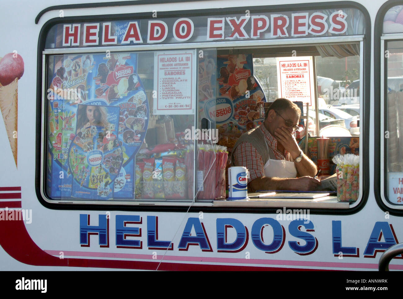e770262555 Ice-cream seller in northern Spain sits in his van reading the paper ...