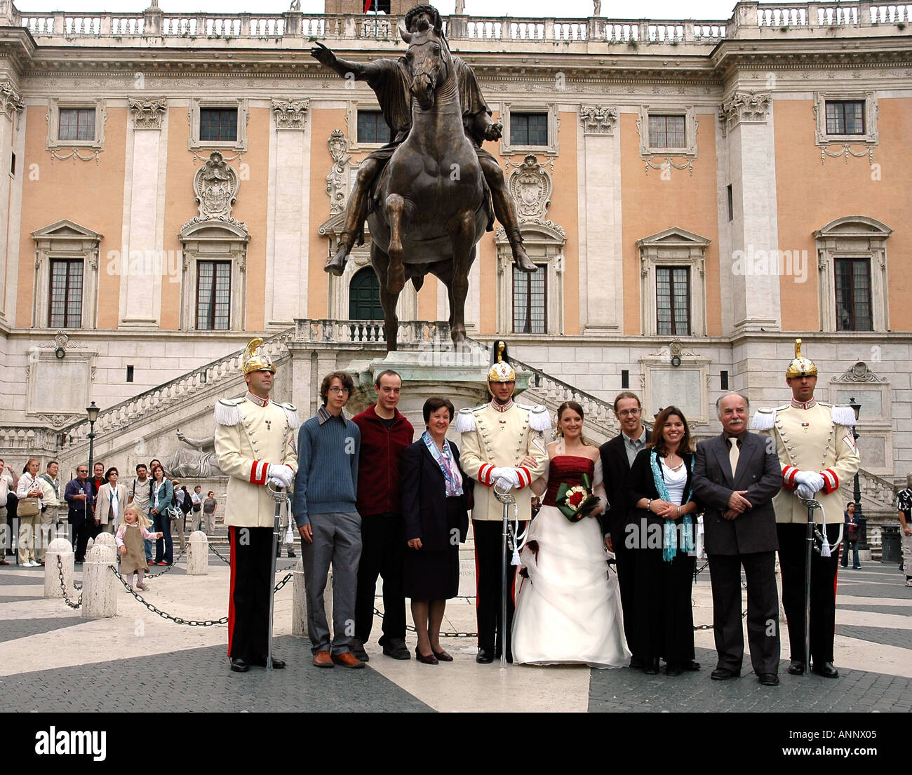 A Presidential Guardsman, his bride escort and family, pose for wedding photos in Rome's Michelangelo-designed Capitoline piazza - Stock Image