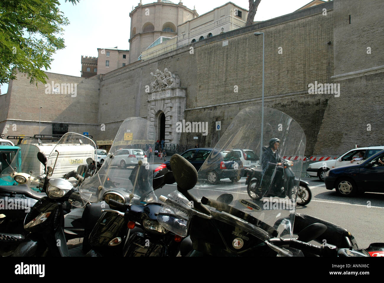 Scooters parked across the street from the highwalled Vatican City museums in Rome - Stock Image