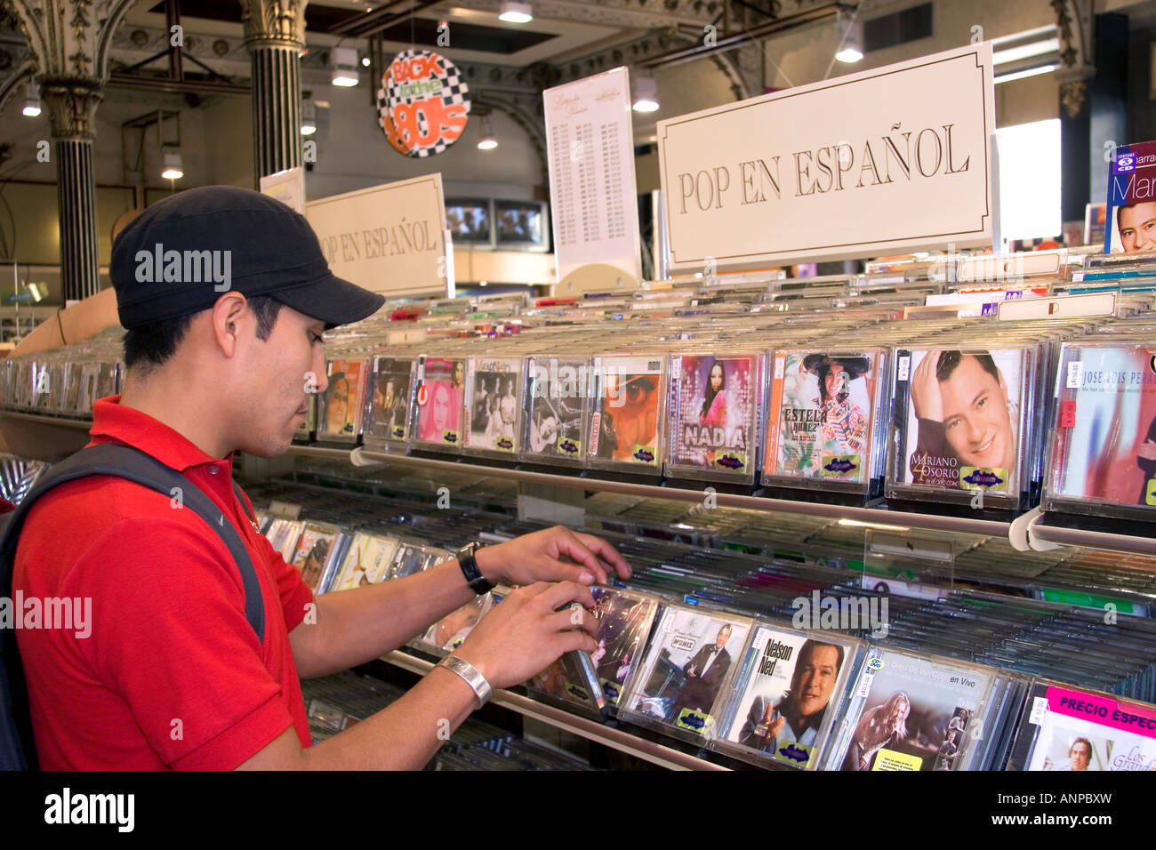A young mexican man shopping for Spanish language cd s at a music store in Mexico City Mexico - Stock Image