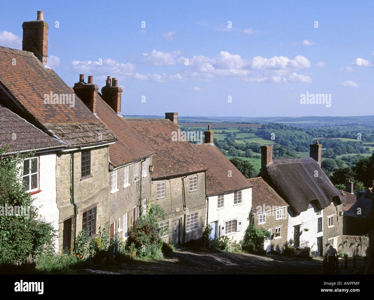 Shaftesbury Gold Hill steep cobbled street with row of old cottages famous location of Hovis bread advert rural landscape beyond - Stock Image