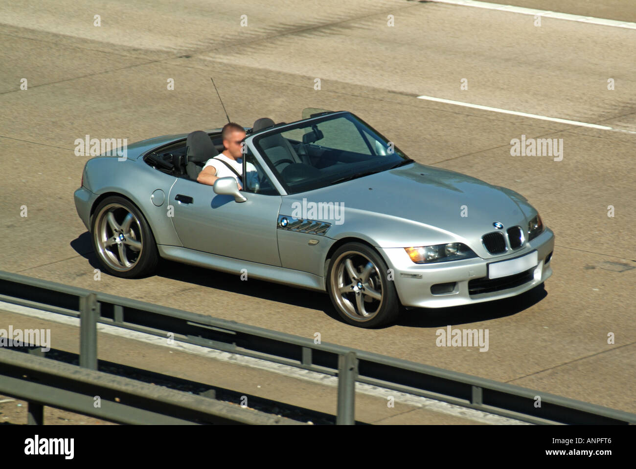 M25 motorway convertible car with hood down obscured numberplate - Stock Image