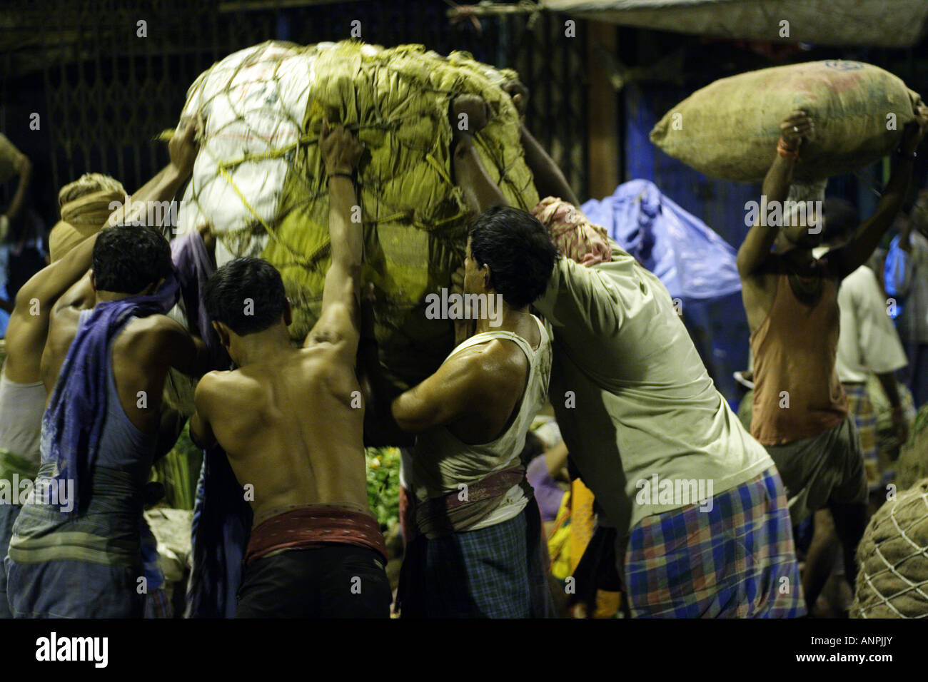 Men lift a heavy weight at the wholesale market for fruit and vegetables in Kolkata, India. - Stock Image