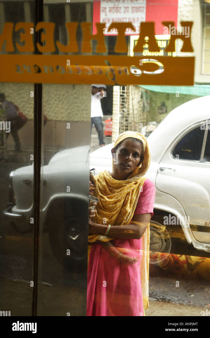 A woman begs from outside of a confectioners, near to Sudder Street, Kolkata, India. She is not permitted to enter Stock Photo