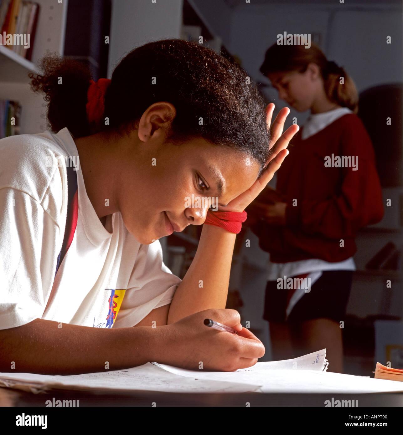 Afro Caribbean junior schoolgirl studies intently in the school library - Stock Image