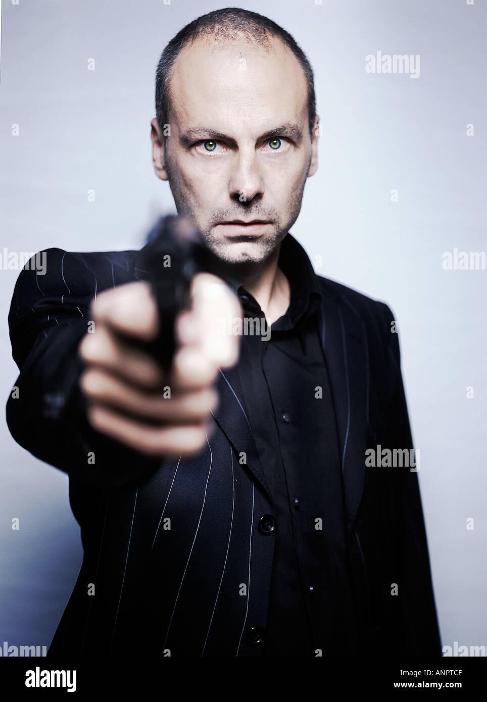 Gangster holding a gun - Stock Image