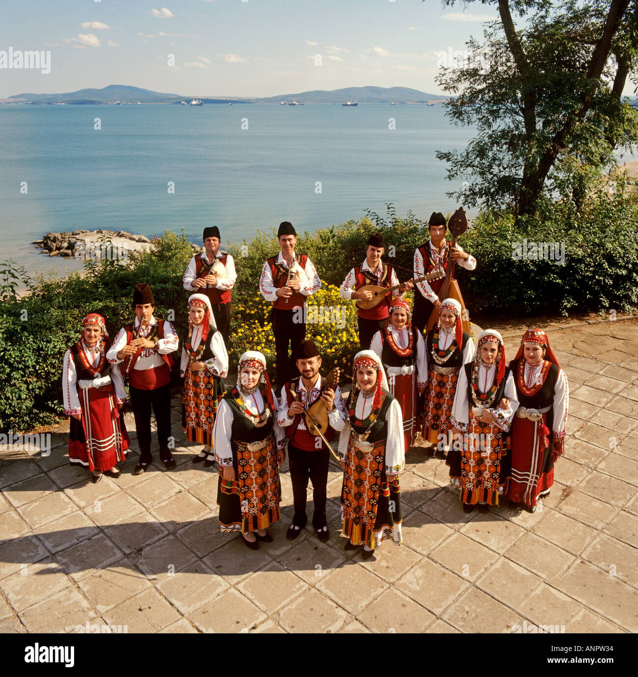 Russian dance and music troupe in traditional folk costume outside in Burgas Bulgaria coastline setting - Stock Image