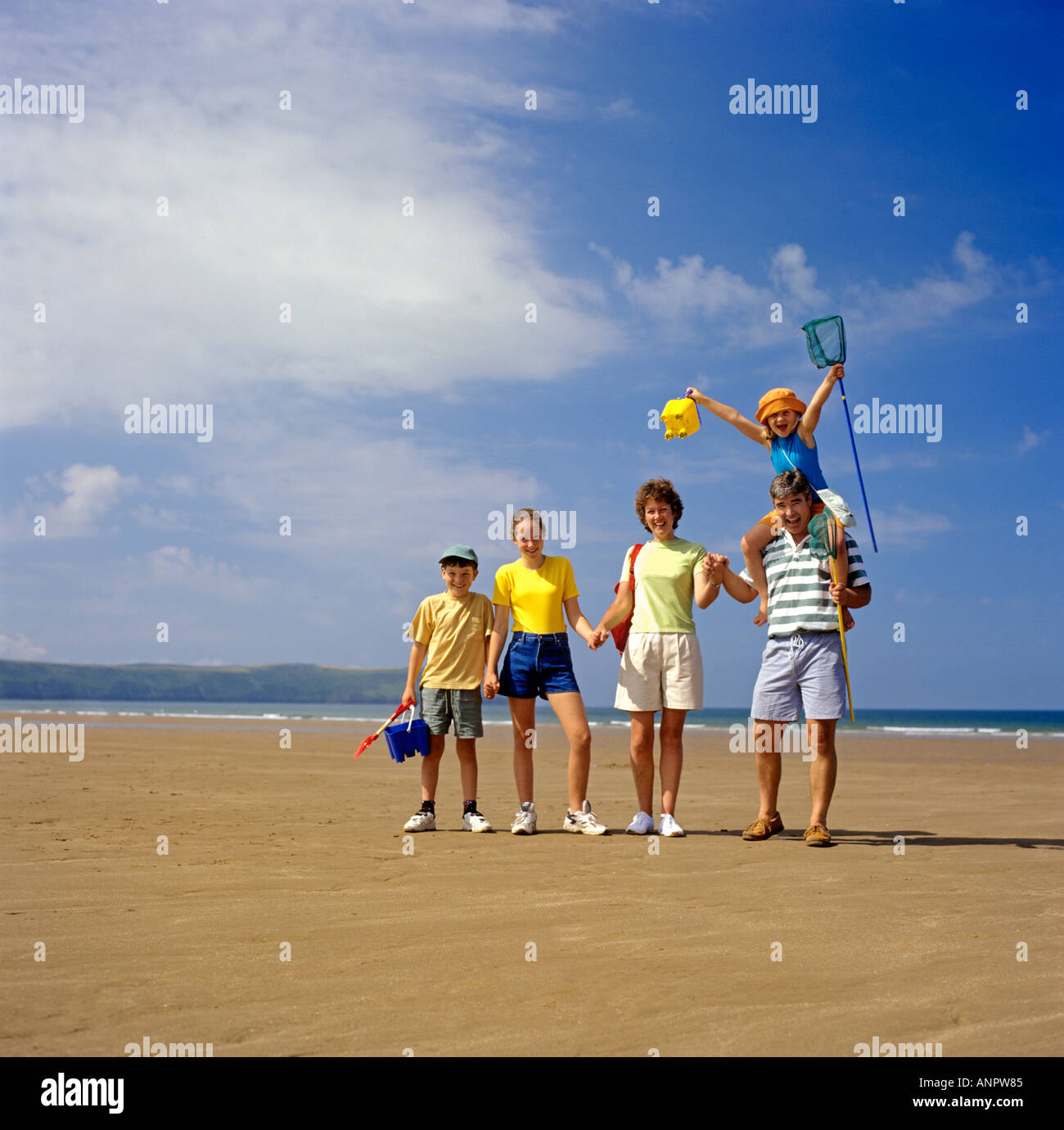 Happy young family of five pose together on Woolacombe Beach during their summer vacation in Devon UK - Stock Image