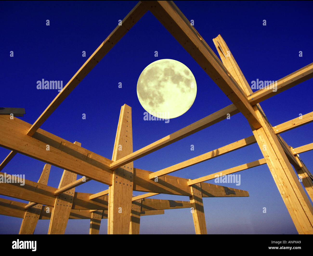 full moon over wood wooden roof construction house building roof truss roof timbers - Stock Image