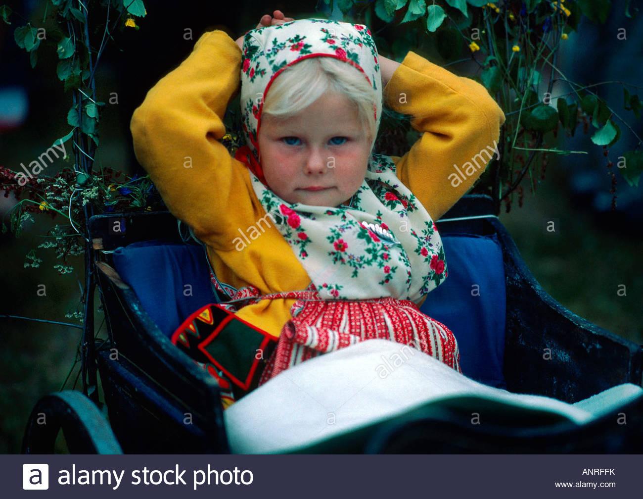 Young Swedish girl at the maypole raising during the Midsummer celebration Siljansnas Dalarna Province Sweden - Stock Image