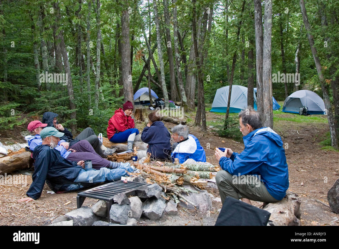 Boundary Waters Canoe Area Wilderness Minnesota Campers relax after dinner at a campsite on Sucker Lake - Stock Image