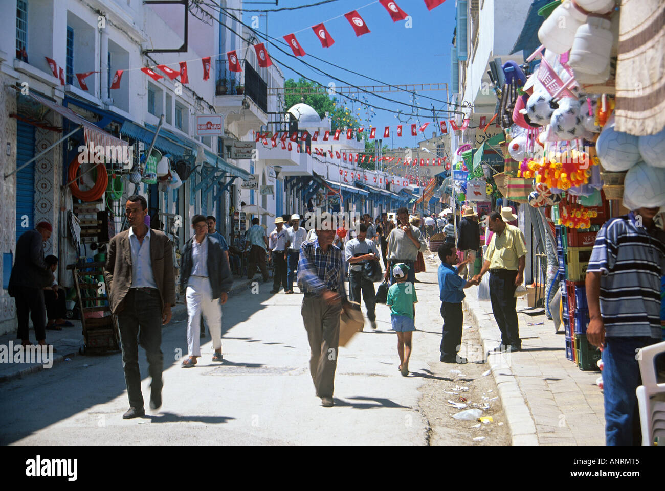 Local shoppers passing along in front of the shops strung about with colourful goods for sale on the Rue Kheireddine Stock Photo