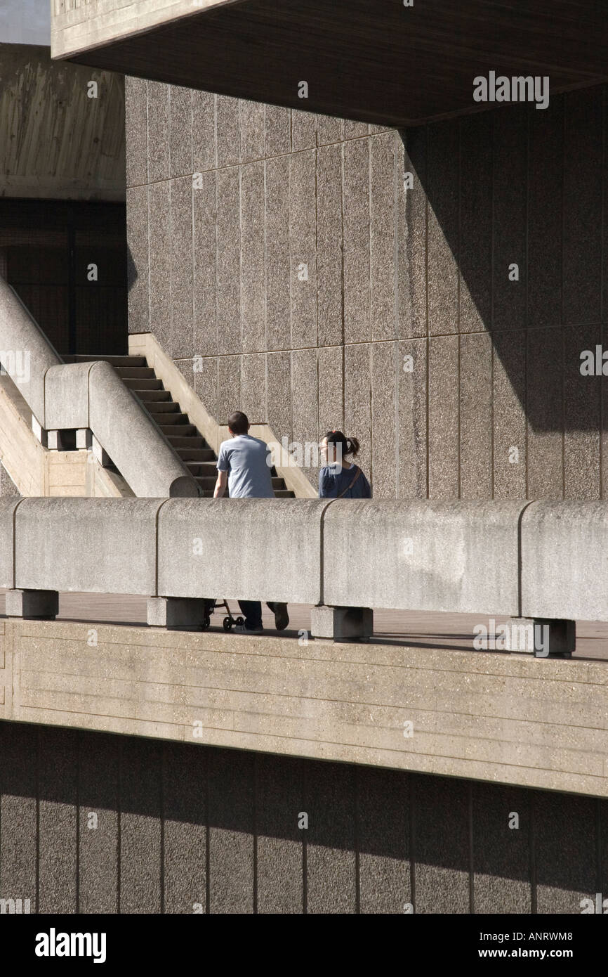 A couple walking amongst the brutalist architecture of the South Bank centre in London - Stock Image